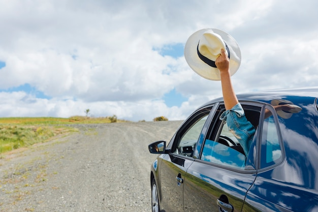 Mano de mujer manteniendo el sombrero en la ventana de la máquina Foto gratis