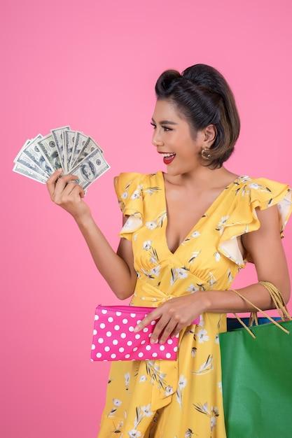 Mano de la mujer de la moda de los jóvenes que sostiene la cartera y los panieres Foto gratis