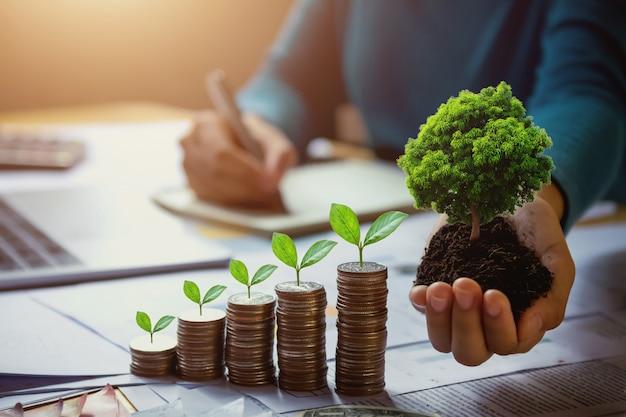 Mano de la mujer de negocios que sostiene el árbol con la planta que crece en monedas. concepto de ahorro de dinero y día de la tierra Foto Premium