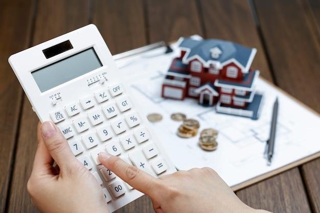 Una mano de la mujer operar una calculadora en frente de un modelo de casa de villa Foto gratis