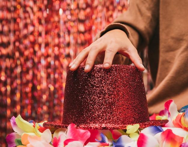 Mano de mujer de primer plano en sombrero rojo Foto gratis