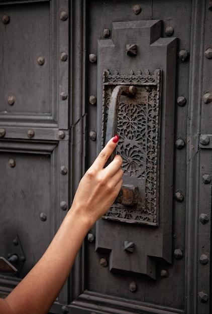 Mano de mujer en la puerta antigua Foto Premium