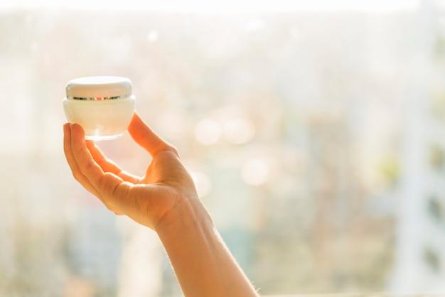 La mano de la mujer que sostiene el envase poner crema cosmético Foto gratis