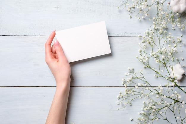 Mano para mujer que sostiene la tarjeta de papel en blanco en fondo de madera azul claro. Foto Premium