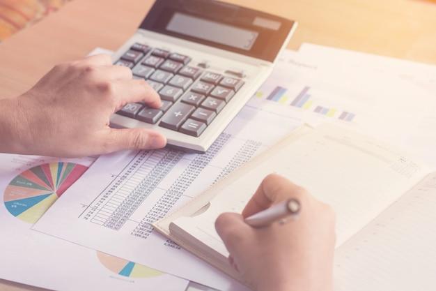 La mano de la mujer que usa la calculadora y la escritura hacen la nota con calcula Foto Premium