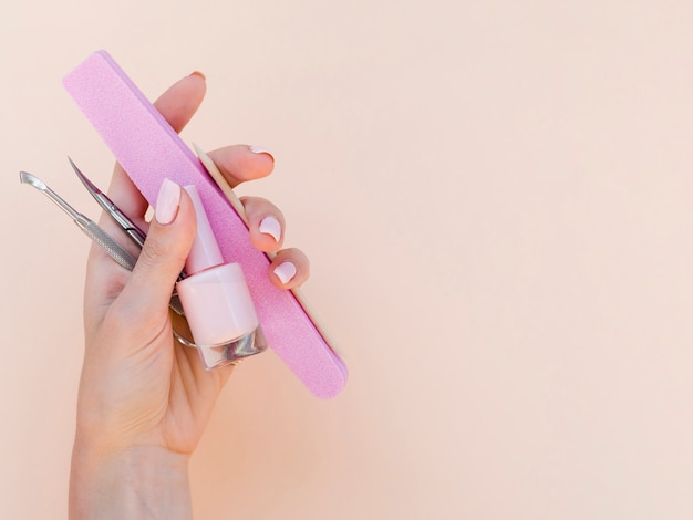Mano de mujer sosteniendo herramientas de manicura Foto gratis