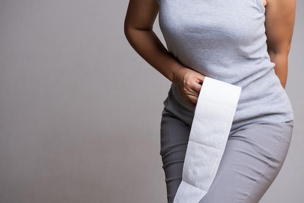 Mano de mujer sosteniendo su parte inferior y papel o rollo de papel higiénico. Foto Premium
