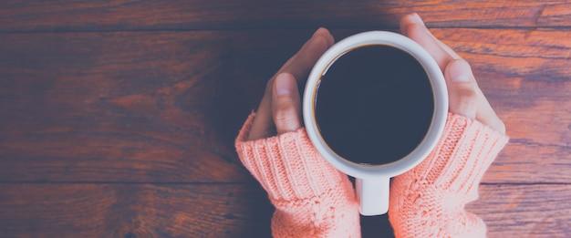 Mano de la mujer en el suéter caliente que sostiene una taza de café en un fondo de madera de la tabla Foto Premium
