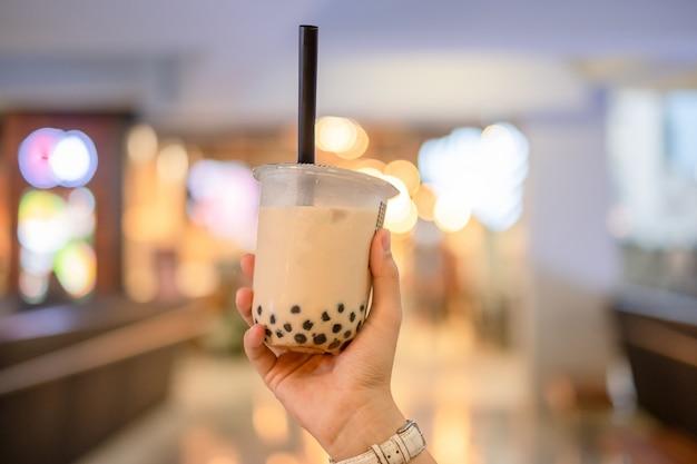 Mano de mujer con té de burbujas de leche helada Foto Premium