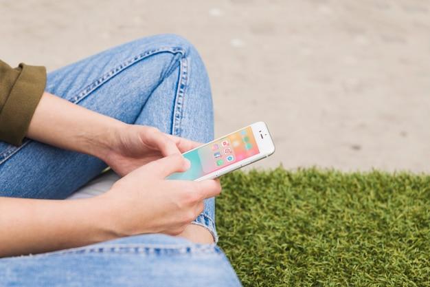 Mano de mujer con teléfono móvil usando la aplicación de redes sociales Foto gratis