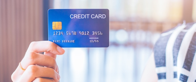 Mano de mujer tiene una tarjeta de crédito azul. Foto Premium