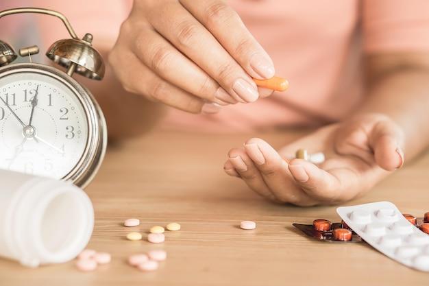 f91c023cc47f Mano de mujer tomando pastillas con reloj en el escritorio ...