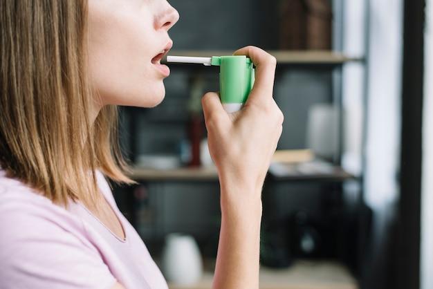 Mano de mujer usando spray para la garganta Foto gratis