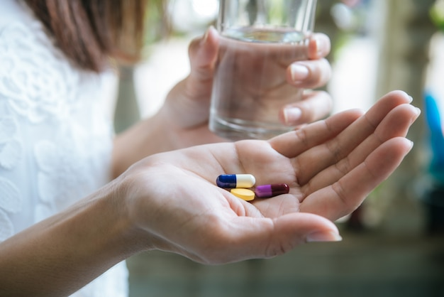 Mano de mujer vierte las pastillas de la medicina fuera de la botella Foto gratis
