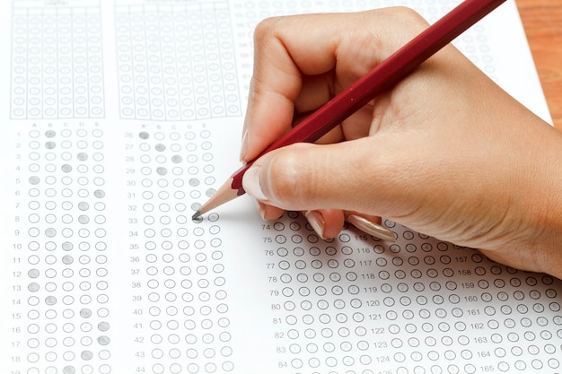 Mano de mujeres con lápiz en forma de prueba estandarizada con respuestas burbujeadas y un lápiz, enfoque o Foto Premium