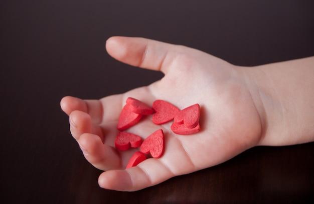 La mano del niño que lleva a cabo corazones rojos en el fondo negro. Foto Premium