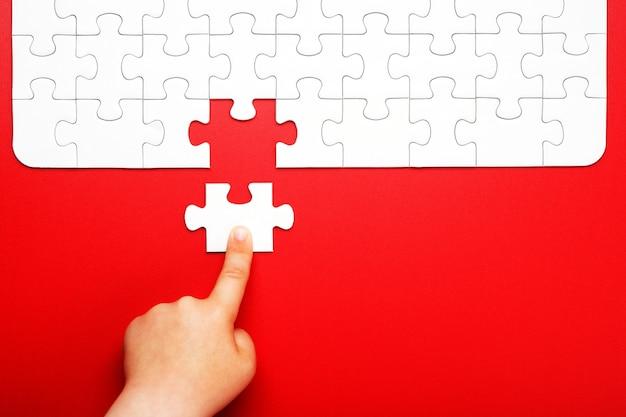 La mano de los niños mueve una pieza de rompecabezas blanco sobre un fondo rojo Foto Premium