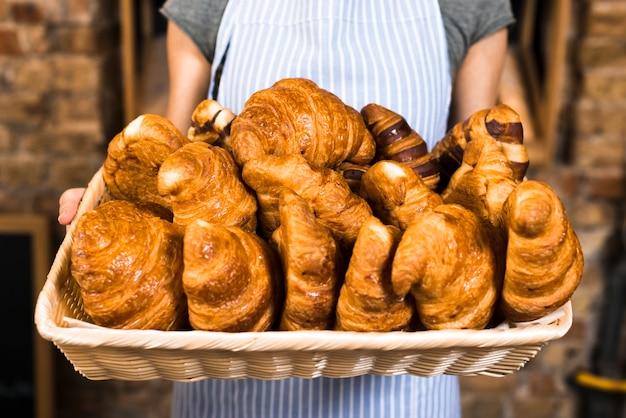 Mano del panadero femenino que sostiene la cesta de croissant al horno Foto gratis