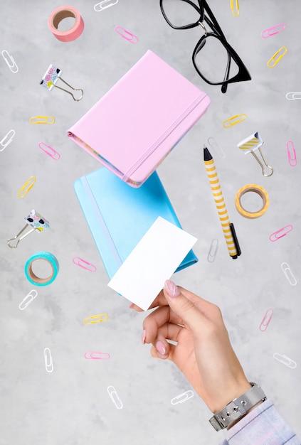 La mano y la papelería de la mujer levitan sobre fondo gris concreto Foto Premium
