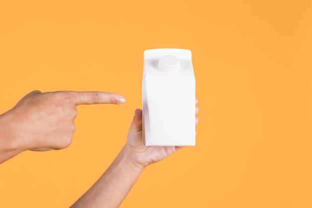 Mano de la persona apuntando sobre tetra pack blanco sobre fondo amarillo Foto gratis