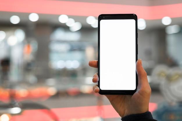 La mano de una persona mostrando una pantalla móvil contra un fondo borroso. Foto gratis