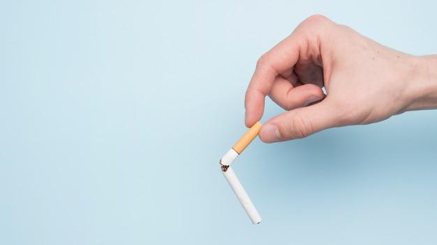 Mano de la persona que muestra cigarrillo roto sobre fondo azul Foto gratis