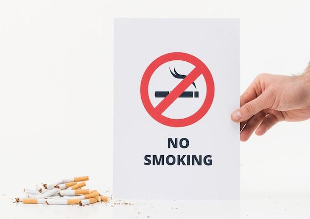 Mano de una persona que muestra el letrero de no fumar cerca de los cigarrillos rotos sobre fondo blanco Foto gratis