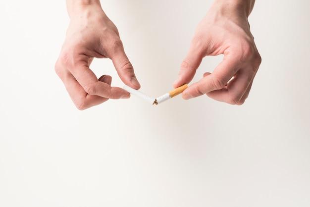 La mano de la persona que rompe el cigarrillo en el fondo blanco Foto Premium