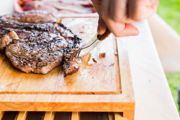 Una mano de la persona que sostiene el cuchillo y el tenedor que corta el filete de carne a la parrilla en la tajadera Foto gratis