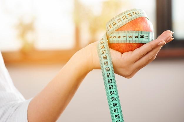Mano de la persona sosteniendo una manzana roja con cinta de medición verde Foto gratis