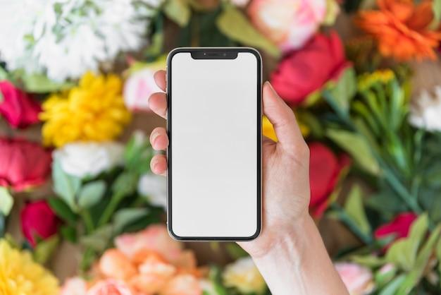 Mano de la persona con el teléfono inteligente cerca de las flores Foto gratis