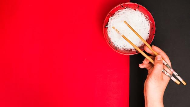 La mano de la persona usa palillos para recoger sabrosos fideos al vapor en un tazón sobre una mesa doble Foto gratis