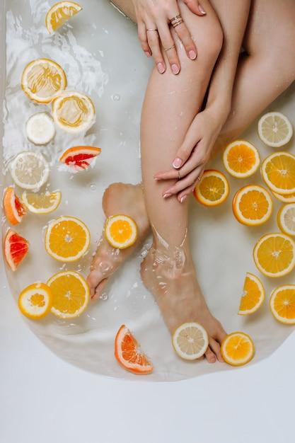 Mano y piernas de la mujer en un baño lleno de agua y varios cítricos cortados Foto Premium