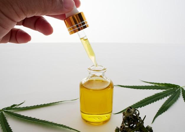 Mano con pipetas y aceite de extracto de cannabis. Foto Premium
