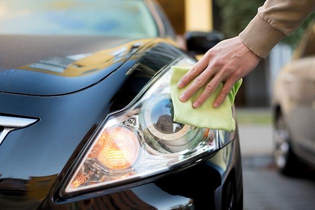Mano con plumero limpiando faros de auto oscuro Foto Premium