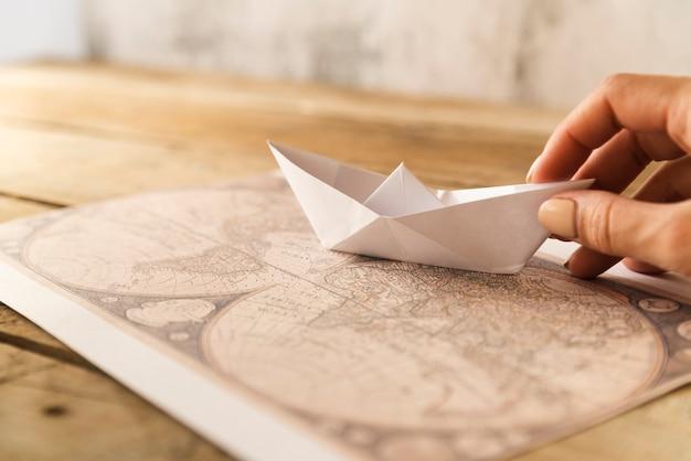 La mano pone el barco de papel en el mapa Foto gratis