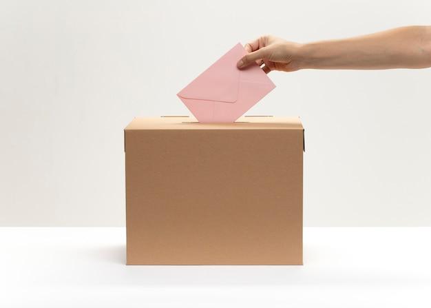 La mano pone el sobre rosado en la casilla de votación Foto gratis