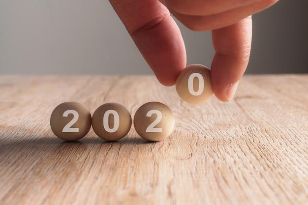 Mano poniendo en 2020 palabra escrita en cubo de madera Foto Premium