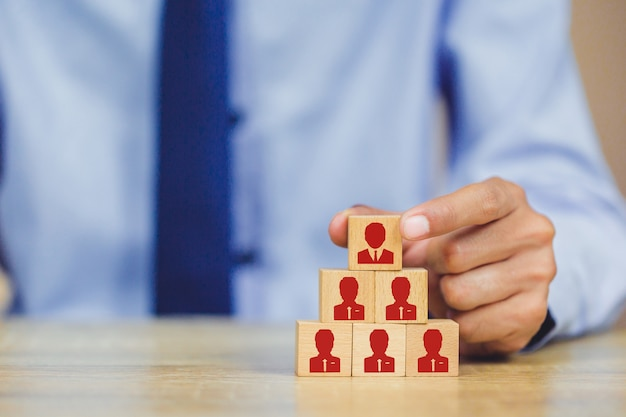 Mano poniendo bloque de cubo de madera en la pirámide superior, gestión de recursos humanos y concepto de negocio de reclutamiento Foto Premium