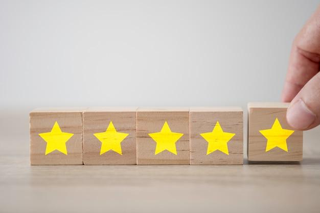 Mano poniendo cinco estrellas amarillas que imprimieron la pantalla en el cubo de madera. encuesta de experiencia del cliente y concepto de comentarios de satisfacción. Foto Premium