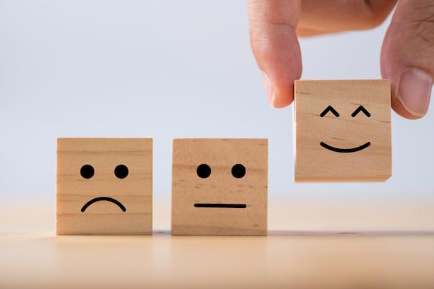 Mano poniendo emoción sonriente entre emoción normal y triste que imprime la pantalla en madera cúbica. encuesta de experiencia del cliente y concepto de comentarios de satisfacción. Foto Premium