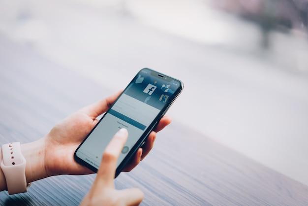 La mano está presionando la pantalla de facebook en apple iphone x, social media. Foto Premium