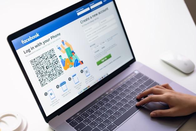 Mano está presionando la pantalla de facebook en la computadora portátil Foto Premium