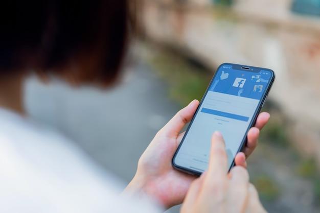 La mano está presionando la pantalla de facebook. Foto Premium