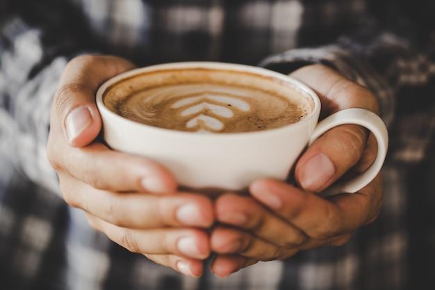 La mano del primer de la hembra que sostiene una taza de café en el café agrega el tono retro del color del filtro Foto gratis