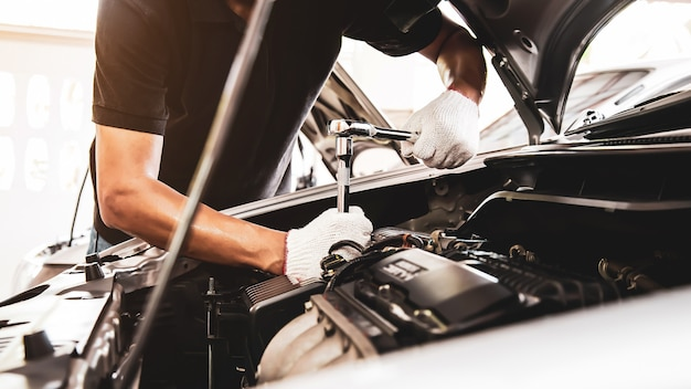 Mano de primer plano de mecánico de automóviles con llave para reparar el motor de un automóvil. Foto Premium
