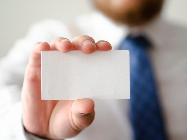Mano de primer plano que muestra una maqueta de tarjeta Foto gratis