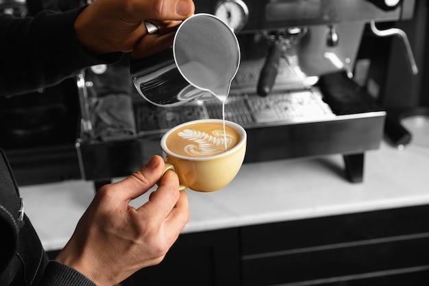 Mano de primer plano vertiendo leche en una deliciosa taza de café Foto gratis