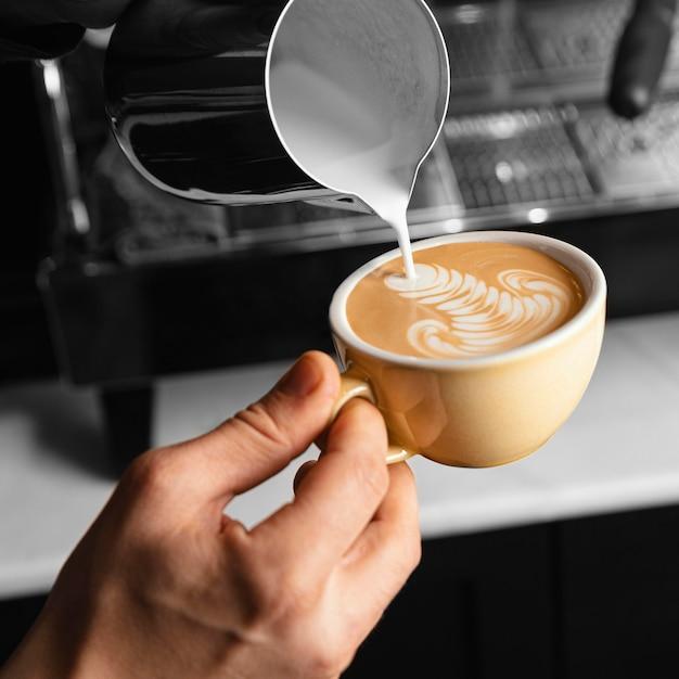 Mano de primer plano vertiendo leche en la taza de café Foto gratis