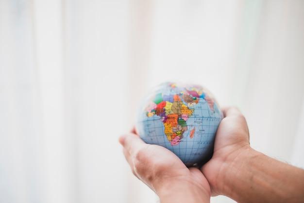 Mano protegiendo globo contra desenfoque de fondo Foto gratis